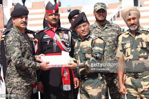 Indian Border Security Force commandant Sudeep presents sweets to Pakistani Wing Commander Bilal on the occasion of the Eid alAdha festival at the...