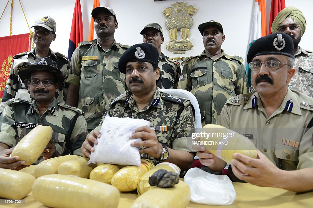 Indian Border Security Force (BSF) Deputy Inspector General (DIG), MF Farooqui (C) and other BSF officers pose with 11 kilogrammes (24 pounds) of confiscated heroin recovered near the border of India and Pakistan, at the BSF head quarters in Khasa, some 15 kilometres from Amritsar on September 2, 2013. Eleven packets of heroin were recovered near the India and Pakistan ,Border Out Post Amar, after the narcotics were allegedly smuggled into the country from neighbouring Pakistan, officials said.