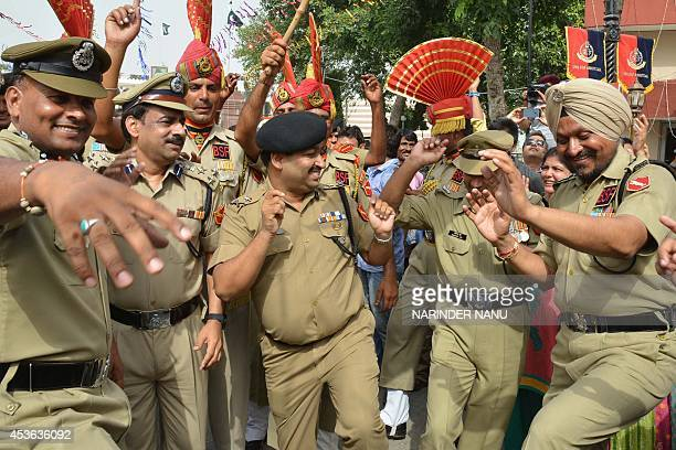 Indian Border Security Force Inspector General Ashok Kumar and BSF officers dance during a ceremony to celebrate Indias 68th Independence Day at the...