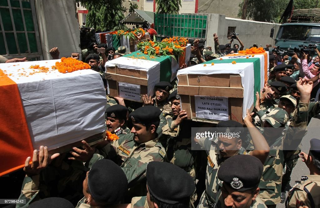 Indian Border Security Force officers carry the coffin of slain soldiers during a wreathlaying ceremony at the BSF headquarters in Jammu on June 13...