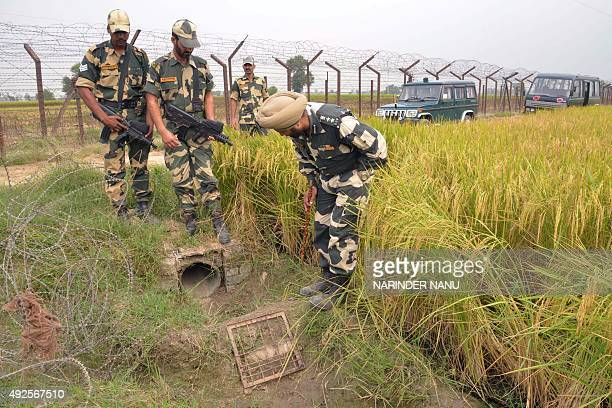 Indian Border Security Force officers inspect the site where 12 packets of confiscated heroin were found near the IndiaPakistan border some 36...