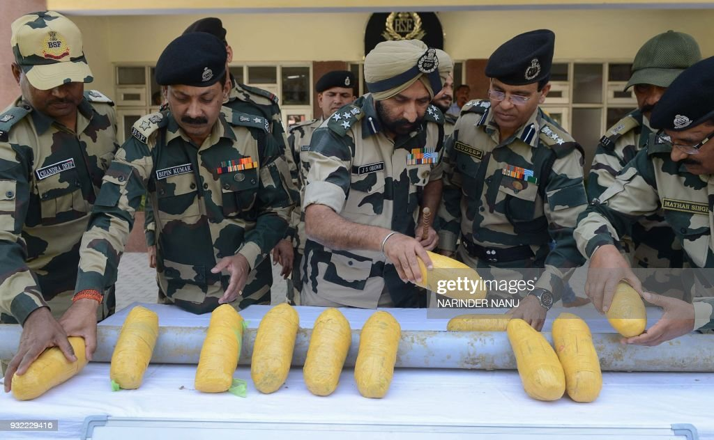 Indian Border Security Force officers show off packets of heroin found near the IndiaPakistan border at the BSF headquarters in Khasa on the...