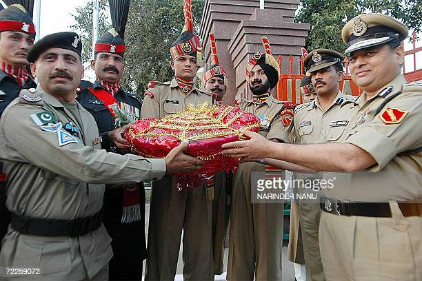 Indian Border Security Force officials headed by Inspector General Border Ranger Arvind Ranjan present sweets to Pakistan Rangers led by LtColonel...