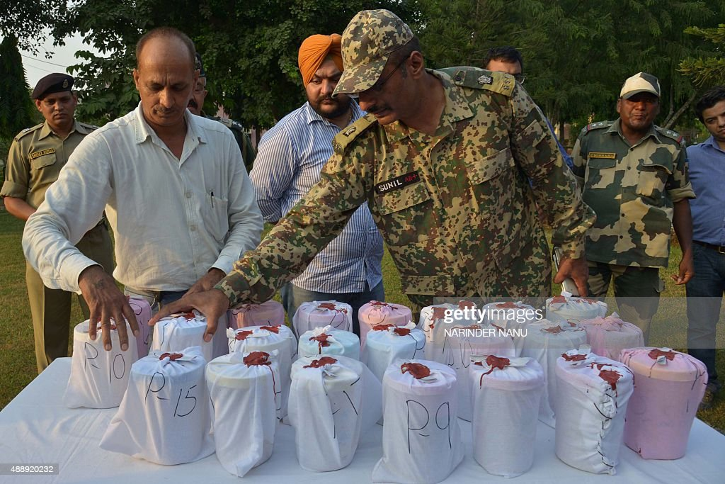 Indian Border Security Force personnel along with customs officials arrange 23 packets of confiscated heroin recovered near the border with Pakistan..