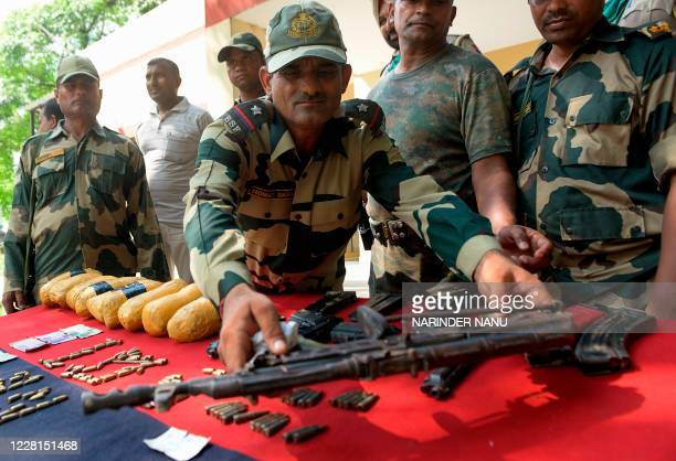 Indian Border Security Force personnel display a recovered AK47 rifle following an overnight operation, at the India-Pakistan Dal Border, around 58...