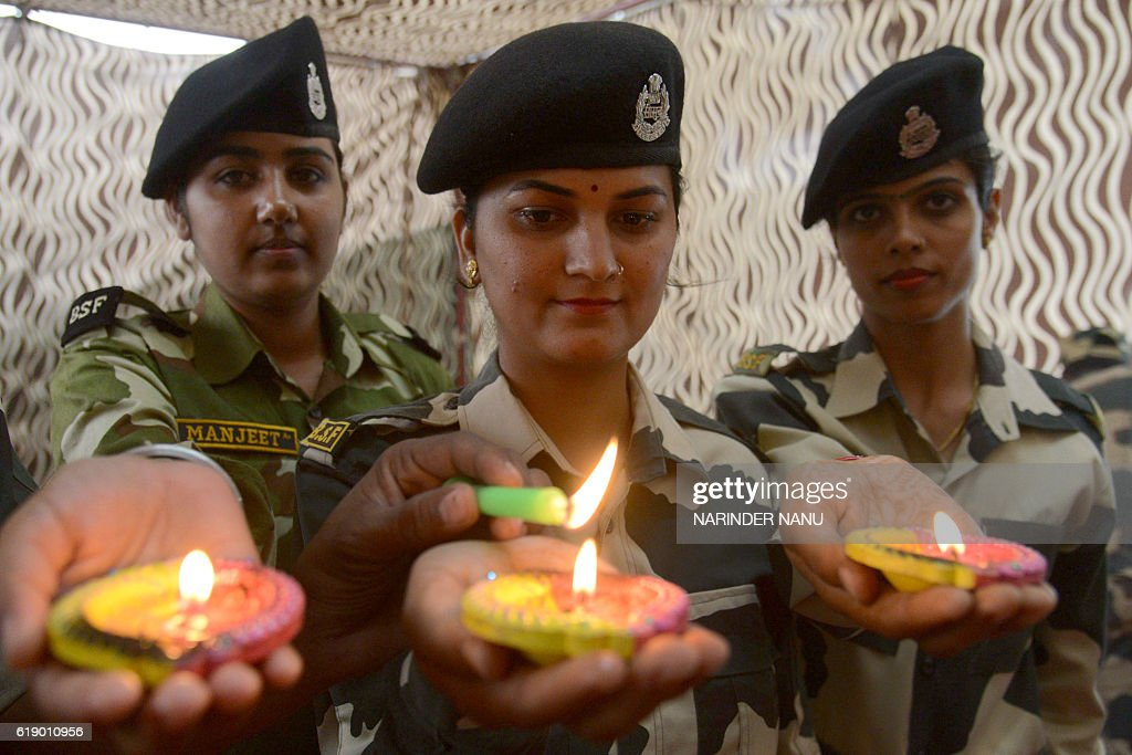 Indian Border Security Force personnel hold earthen lamps on the eve of the Diwali festival at the IndiaPakistan Wagah Border on October 29 2016...