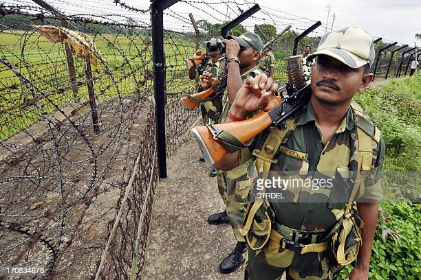 Indian Border Security Force personnel look on through a barb wire fence during a security patrol on the Bangladesh boarder at the Lankamura boarder...