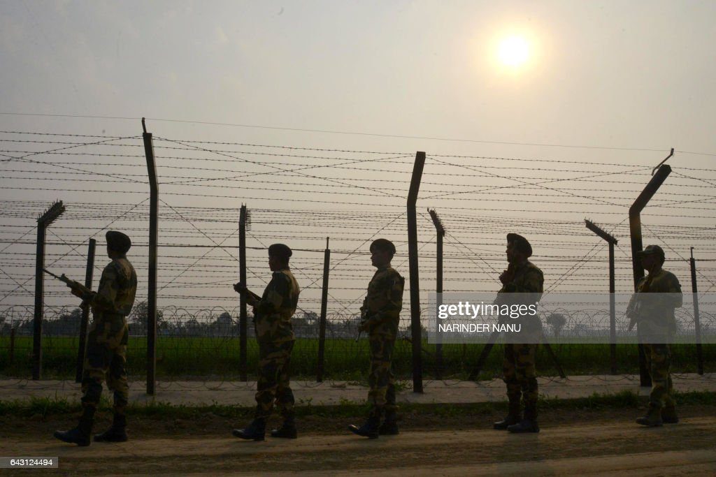 Indian Border Security Force personnel patrol along a fence at the IndiaPakistan border at Wagah some 35kms from Amritsar on February 20 2017 / AFP /.