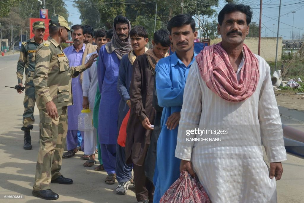 Indian Border Security Force personnel stand next to released Pakistani prisoners waiting to cross the IndiaPakistan border at Wagah near Amritsar on.