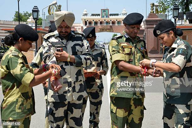 Indian Border Security Force personnel tie a sacred thread or 'rakhi' onto the wrists of BSF Company Commander Jaswinder Kang and BSF Commandant...