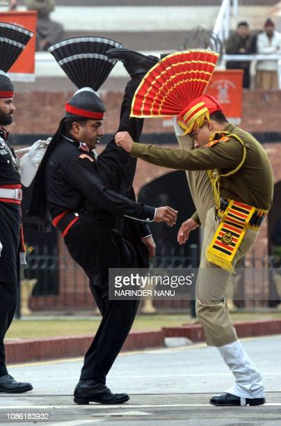 Indian Border Security Force personnel wearing brown uniforms and Pakistani Rangers wearing black uniforms perform while they take part in the...