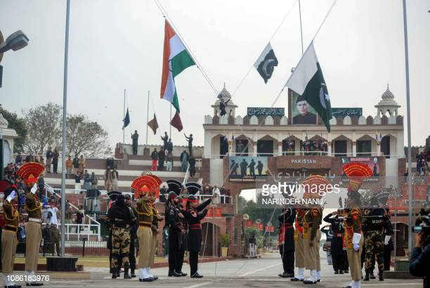 Indian Border Security Force personnel wearing brown uniforms and Pakistani Rangers wearing black uniforms take part in the Beating Retreat ceremony...