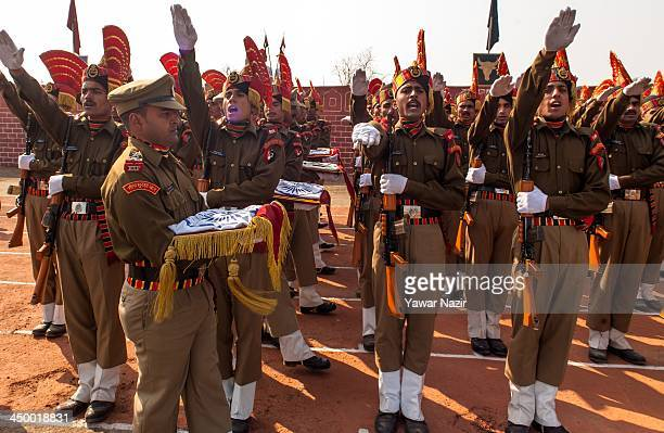 Indian Border Security Force raise their hands a they take oath during their passing out parade on November 16 2013 in Humhama on the outskirts of...
