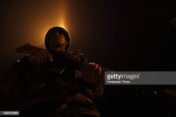 Indian Border Security Force soldier stand guard during night patrol near the fenced border with Pakistan at Abdullian on January 14 2013 about 40...