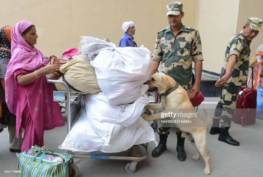 Indian Border Security Force soldiers and a sniffer dog check the luggage of Pakistani nationals crossing the IndiaPakistan border at Wagah about...