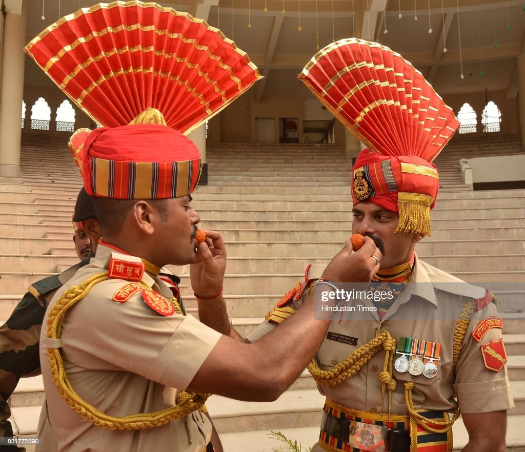 Indian Border Security Force soldiers offer sweets to each other as they celebrate India's 71st Independence Day at the IndiaPakistan Wagah Border