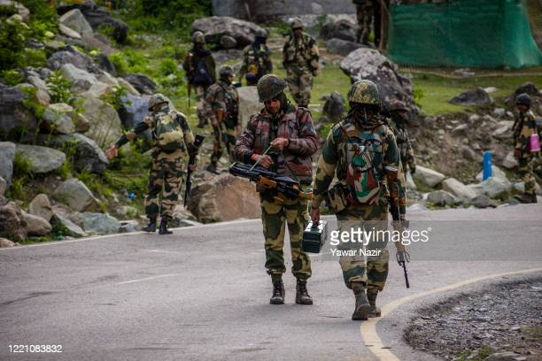 Indian Border Security Force soldiers patrol a highway as Indian army convoy passes through on a highway leading towards Leh, bordering China, on...