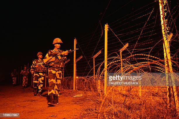 Indian Border Security Force soldiers patrol along the border fence at an outpost along the IndiaPakistan border in Abdulian 38 kms southwest of...