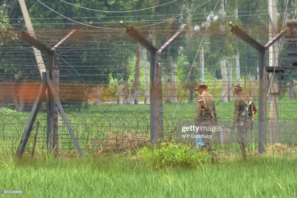 Indian Border Security Force soldiers patrol along the IndiaPakistan border in Wagah some 35km from Amritsar on July 25 2017 Security forces along...