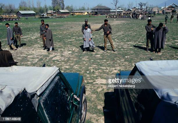 Indian Border Security Force soldiers show suspected militants to people in a line of parked military vehicles, Srinagar, India, July 28, 1994.