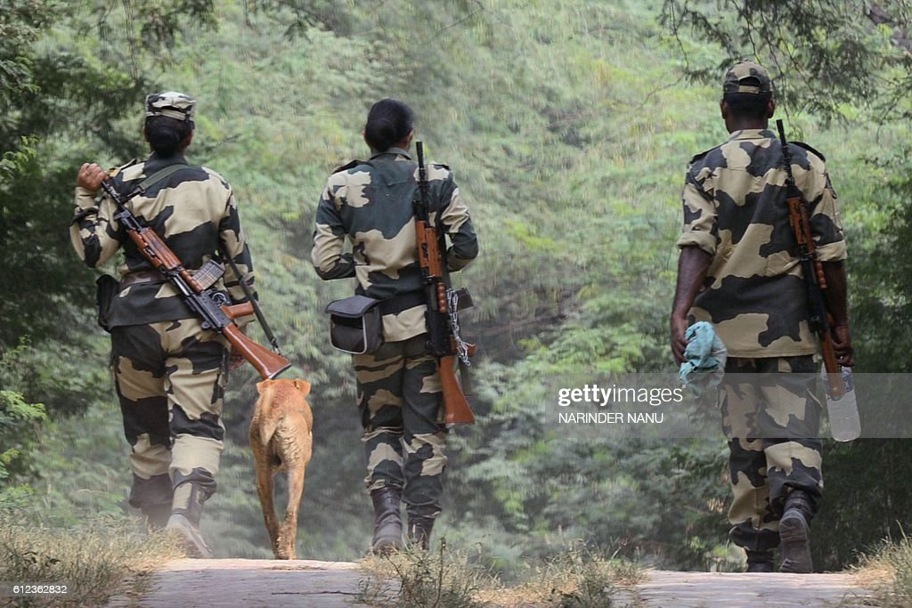Indian Border Security Force soldiers walk near the IndianPakistan border at Rear Kakkar about 40km from Amritsar on October 4 2016 / AFP / NARINDER..