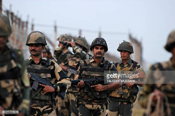 Indian Border Security Force soldiers walk with weapon during a patrol at the IndiaPakistan border in RS Pora southwest of Jammu on October 3 2016 /...