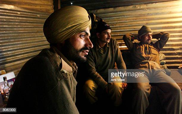 Indian Border Security Force soldiers watch the Indian cricket team play Pakistan in the first oneday international cricket match held in Karachi...