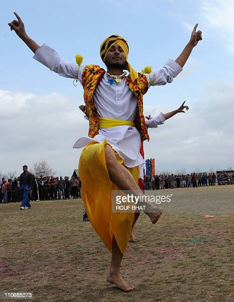 Indian Border Security Force soldiers wearing traditional Punjabi dress dance as they celebrate 'Holi' at their headquarters in Srinagar on March...