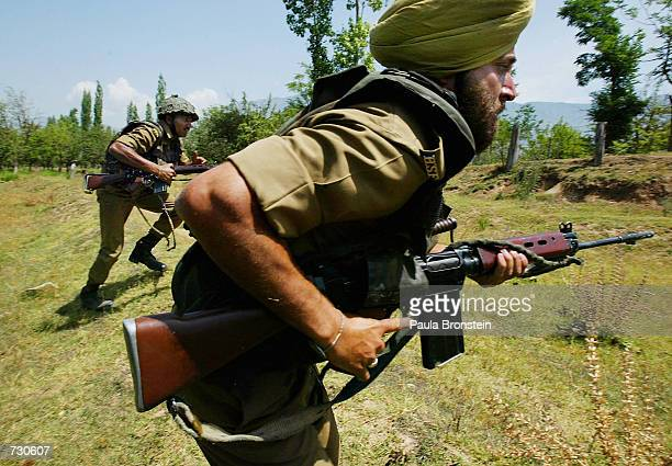 Indian Border Security Force soliders launch a raid on a house during a mock training exercise in counterinsurgency June 14 2002 near Srinagar...
