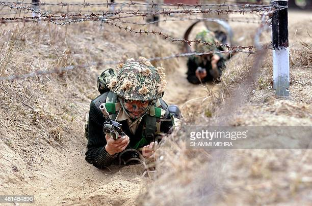 Indian Border Security Force woman commandos crawl under barbed wire during an excercise at the Kharkan Training Camp at Hoshiarpur around 60 kms...