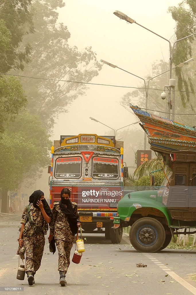 Indian Border Security Force women personnel walk through a dust storm at the IndiaPakistan Wagah Border in India`s northwestern state of Punjab on...
