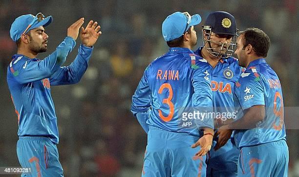 Indian bowler Amit Mishra celebrates with captain Mahendra Singh Dhoni and teammates Suresh Raina and Virat Kohli after taking the wicket of...