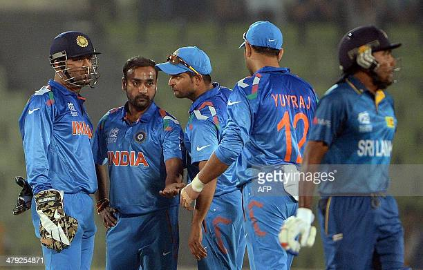 Indian bowler Amit Mishra celebrates with team captain Mahendra Singh Dhoni and teammates Suresh Raina and Yuvraj Singh after taking the wicket of...