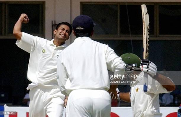 Indian bowler Anil Kumble celebrates the dismissal of Pakistani batsman Taufiq Umar who holds his bat as Indian cricketer Rahul Dravid looks on...