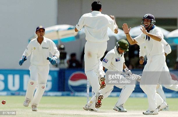 Indian bowler Anil Kumble celebrates with teammates after dismissing Pakistani batsman Taufiq Umer during the fourth day of the first Test match...