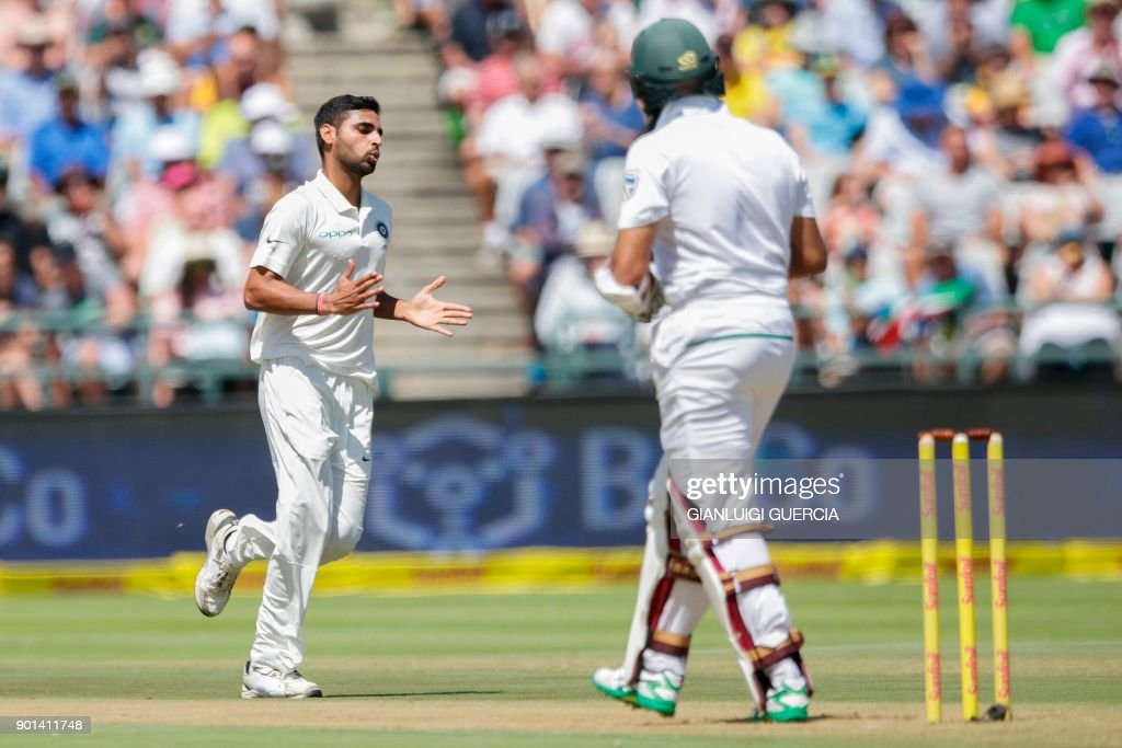 Indian bowler Bhuvneshwar Kumar celebrates the dismissal of South African batsman Hashim Amla (R) during Day One of the First Test cricket match between South Africa and India at Newlands cricket ground on January 5, 2018 in Cape Town. /