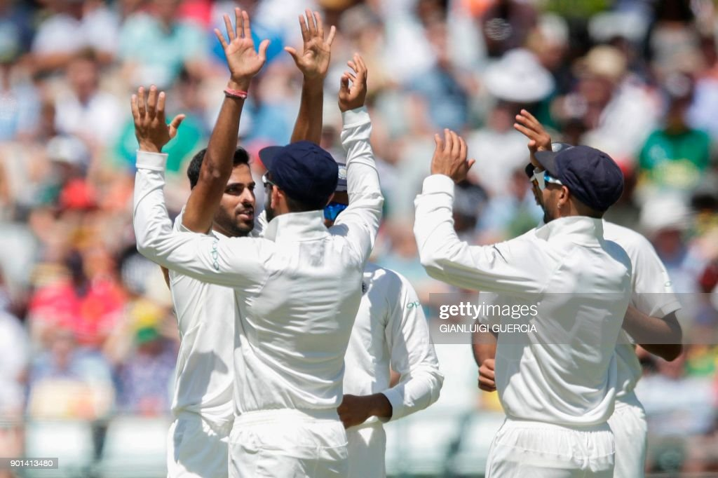 Indian bowler Bhuvneshwar Kumar (L) celebrates the dismissal of South African batsman Hashim Amla (not in picture) during Day One of the First Test cricket match between South Africa and India at Newlands cricket ground on January 5, 2018 in Cape Town. /