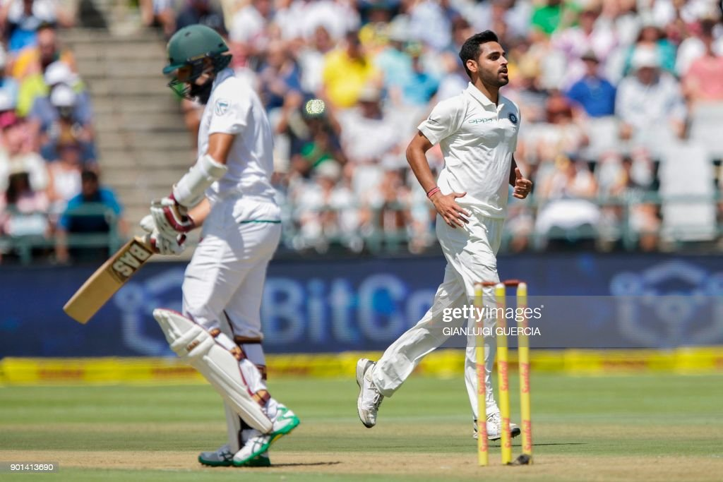 Indian bowler Bhuvneshwar Kumar (R) celebrates the dismissal of South African batsman Hashim Amla (L) during Day One of the First Test cricket match between South Africa and India at Newlands cricket ground on January 5, 2018 in Cape Town. /
