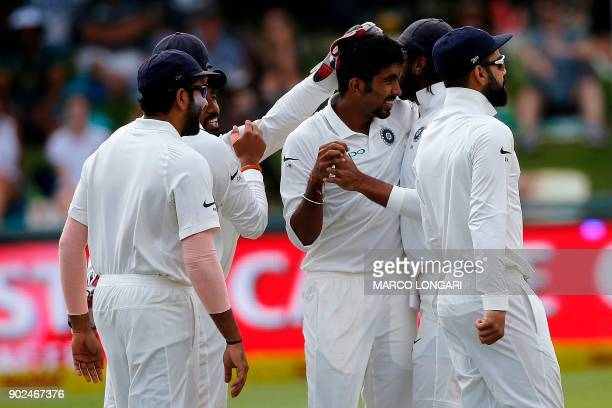 Indian bowler Jasprit Bumrah celebrates with teammates after the dismissal of South African batsman Faf du Plessis during the fourth day of the first...
