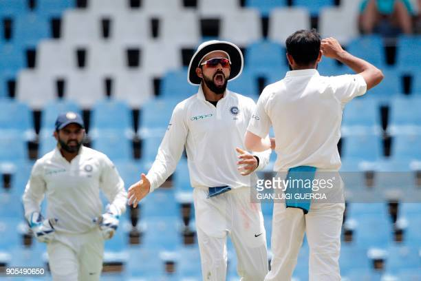 Indian bowler Mohammed Shami and Captain Virat Kohli celebrate the dismissal of South African batsman Quinton de Kock during the fourth day of the...