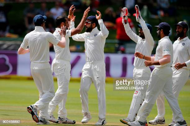 Indian bowler Mohammed Shami celebrates with teammates after the dismissal of South African batsman Kagiso Rabada during the fourth day of the first...