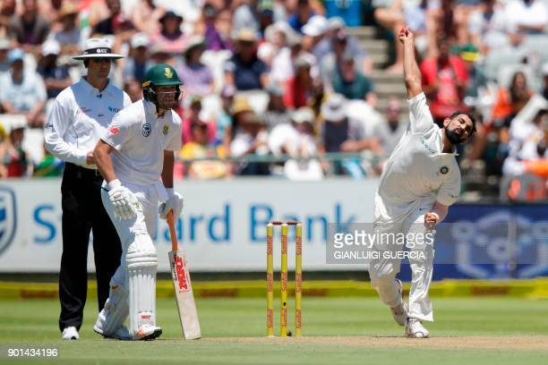 Indian bowler Mohammed Shami delivers a ball to South African batsman Faf du Plessis as South African batsman AB de Villiers looks on during day one...