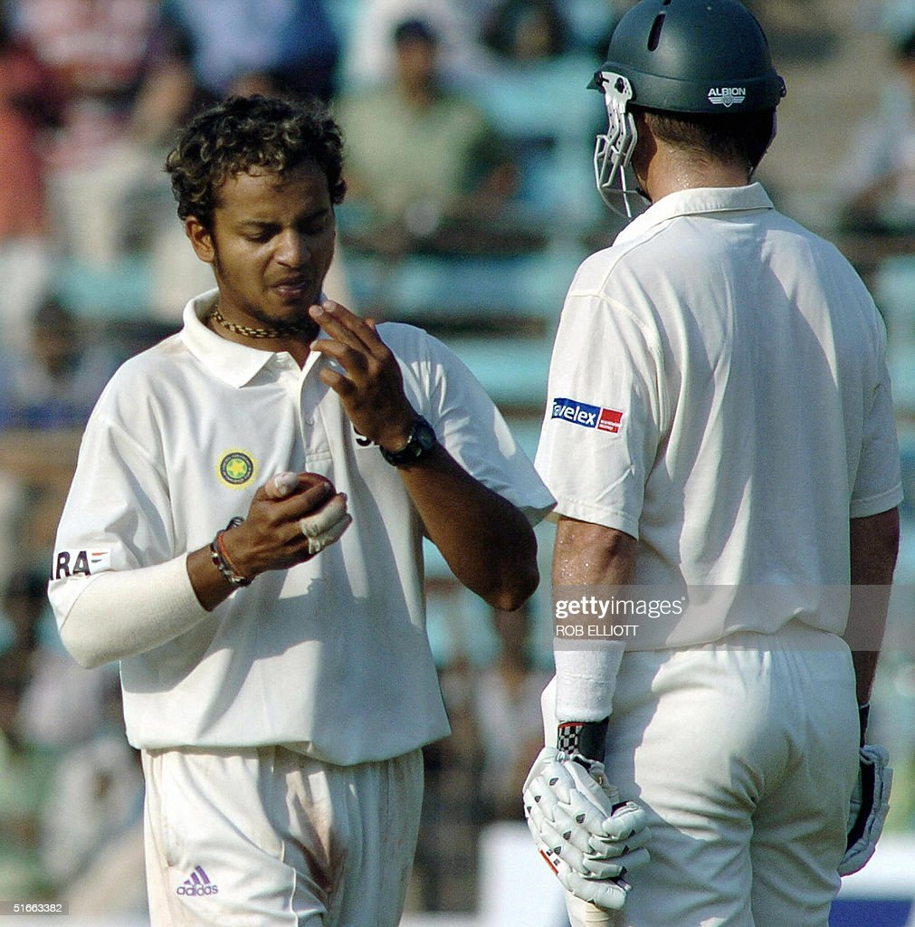 Indian bowler, Murlai Kartik (L) licks his fingers to rub on the ball before a delivery at the Wankhede Stadium, Bombay, 04 November 2004, on day two of the fourth Test between Australia and India. Australia were all out for 184 runs chasing India's first innings, all out for 104 runs. AFP PHOTO/Rob ELLIOTT