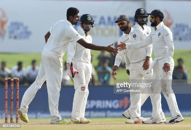 Indian bowler Ravichandran Ashwin celebrates with his teammates after he dismissed Sri Lankan batsman Nuwan Pradeep during the fourth day of the...