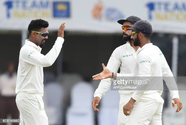 Indian bowler Ravindra Jadeja celebrates with his teammates after he dismissed Sri Lankan batsman Angelo Mathews during the third day of the first...