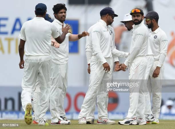 Indian bowler Umesh Yadav celebrates with his teammates after dismissing Sri Lankan batsman Danushka Gunathilaka during the fourth day of the first...