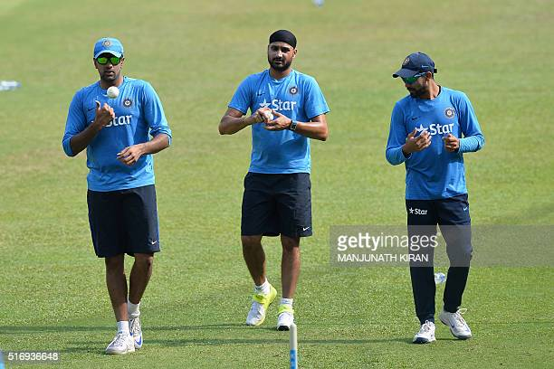 Indian bowlers Ravi Chandran Ashwin Harbhajan Singh and Ravindra Jadeja take part in a net practice session on the eve of their match against...