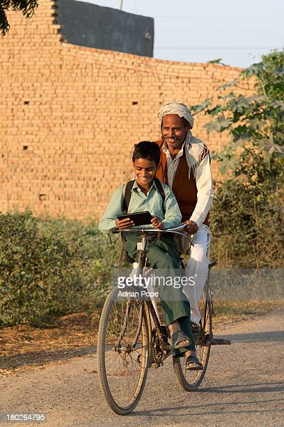 Indian boy and father riding to school