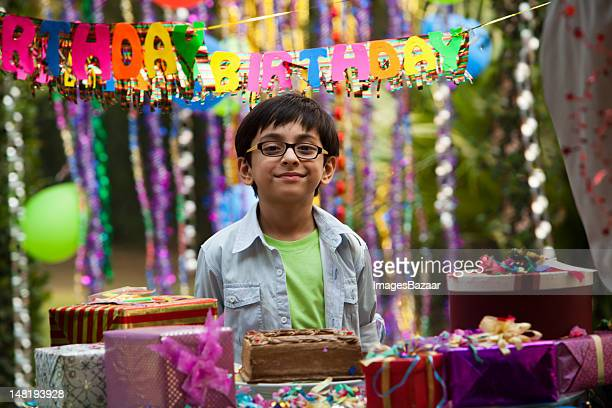 Indian boy (6-7) smiling during birthday party