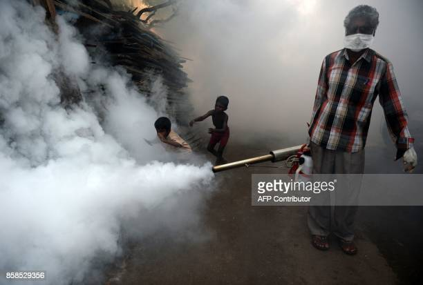 Indian boys follow a municipal worker fumigating the area to prevent mosquitos from breeding in Chennai on October 7 2017 Several cases of the...